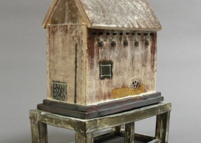 Sculpture titled House with Black Windows and Stand, 10 x 7&1/2 x 4&1/2